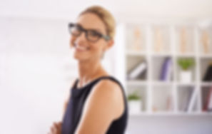 Smiling women with glasses posing in front of white shelf