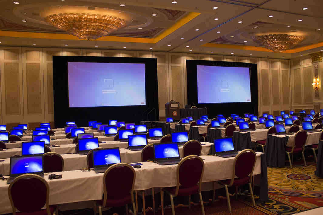 Two big projector screens at a conference