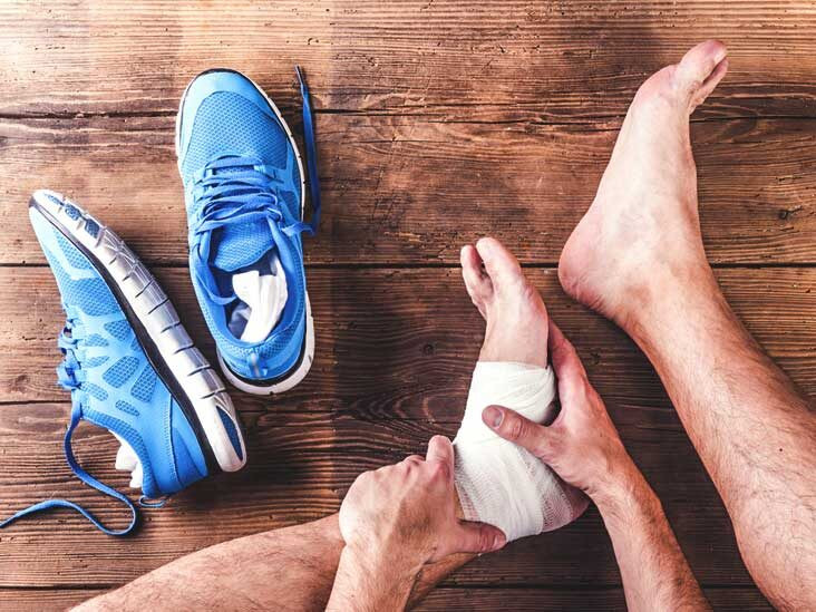 A male runner wrapping a tensor bandage around his left ankle