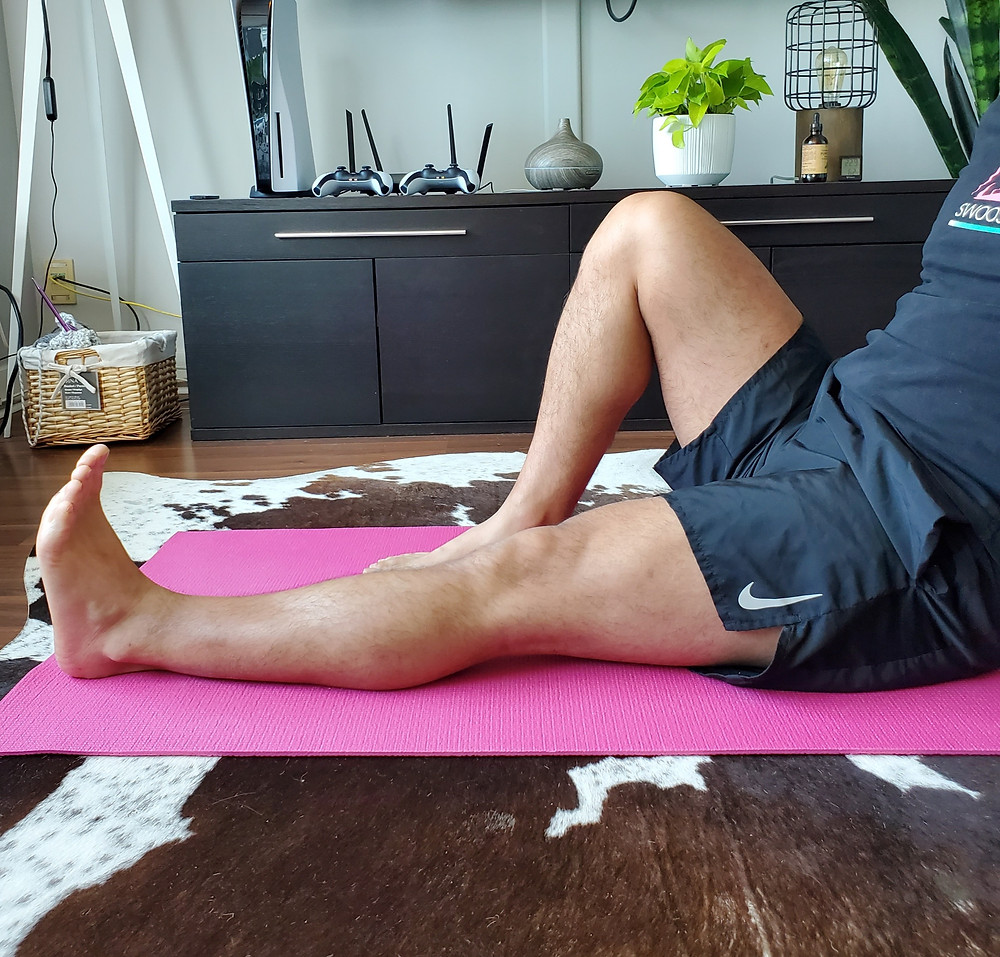 Physiotherapist in a seated position with knee straight flexing his quadriceps