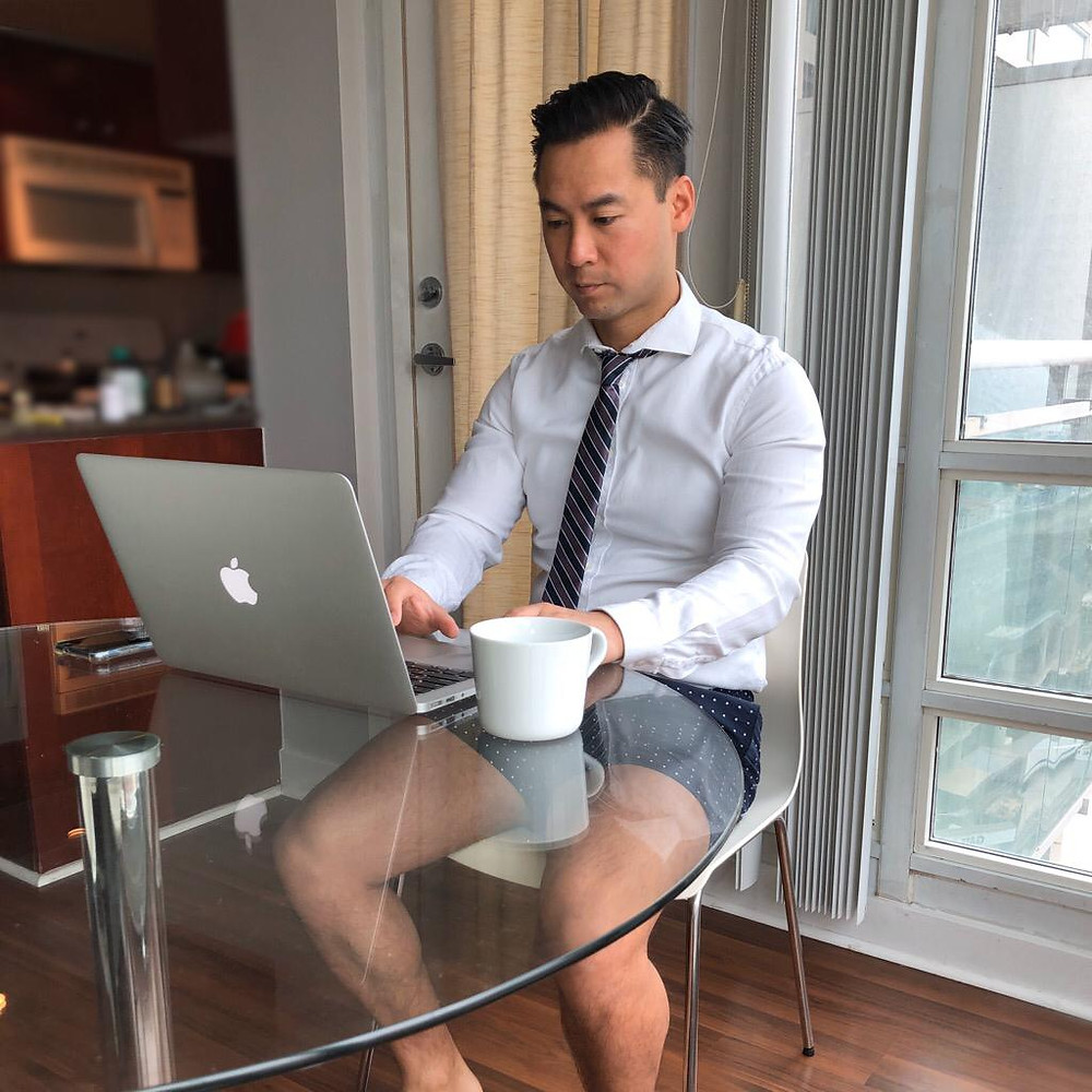 During Covid 19, physiotherapist working from home wearing dress shirt, tie, and shorts