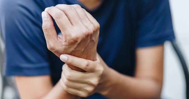 Man holding sore right wrist