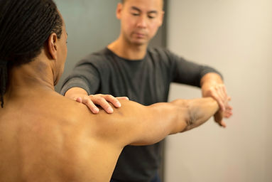 Physiotherapist is testing his patient's shoulder strength