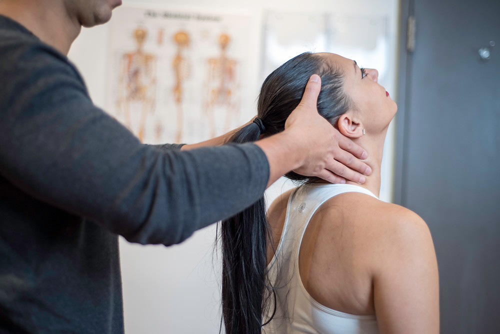 Rebuild physiotherapist checking patient's neck range of motion