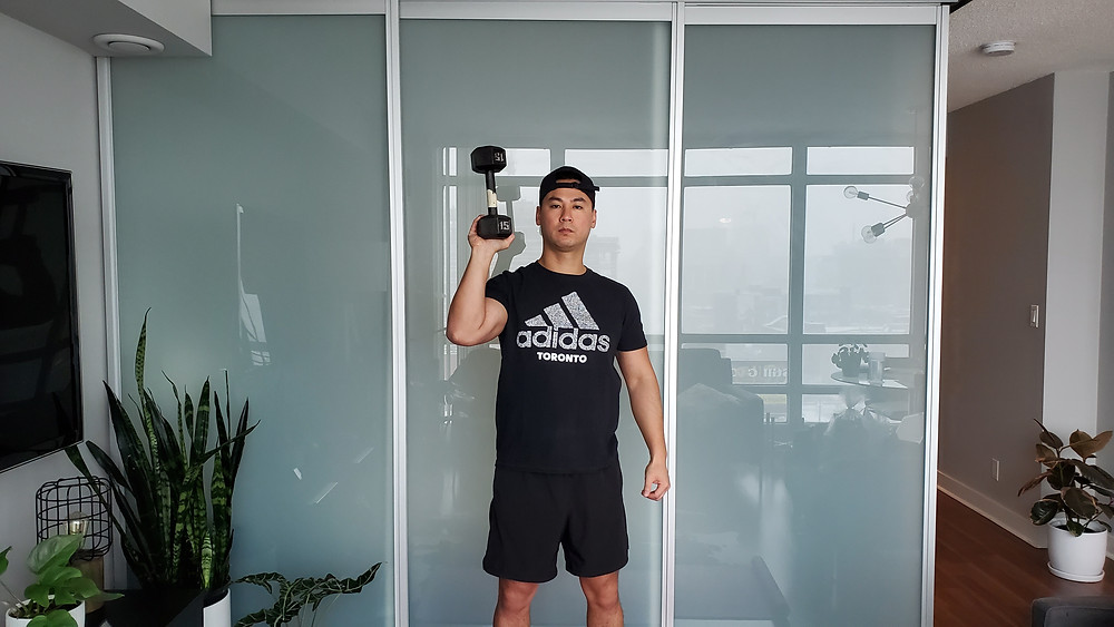 Physiotherapist demonstrating how to perform an overhead press while holding an inverted dumbbell
