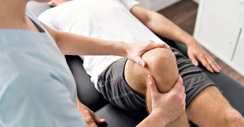 Physiotherapist assessing a man's knee after a total knee replacement surgery