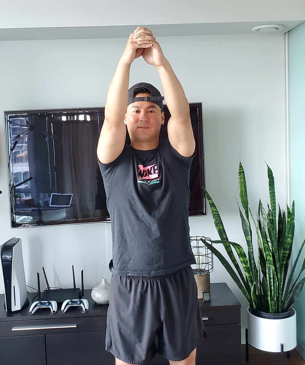 Man standing up and clasping both hands together and reaching up overhead