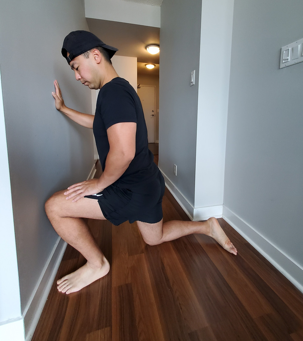 Physiotherapist in a lunge position in front of a wall