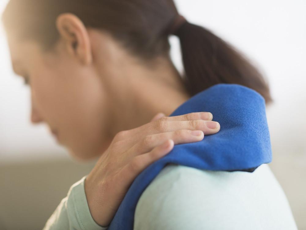 Women placing cold compress onto sore shoulder