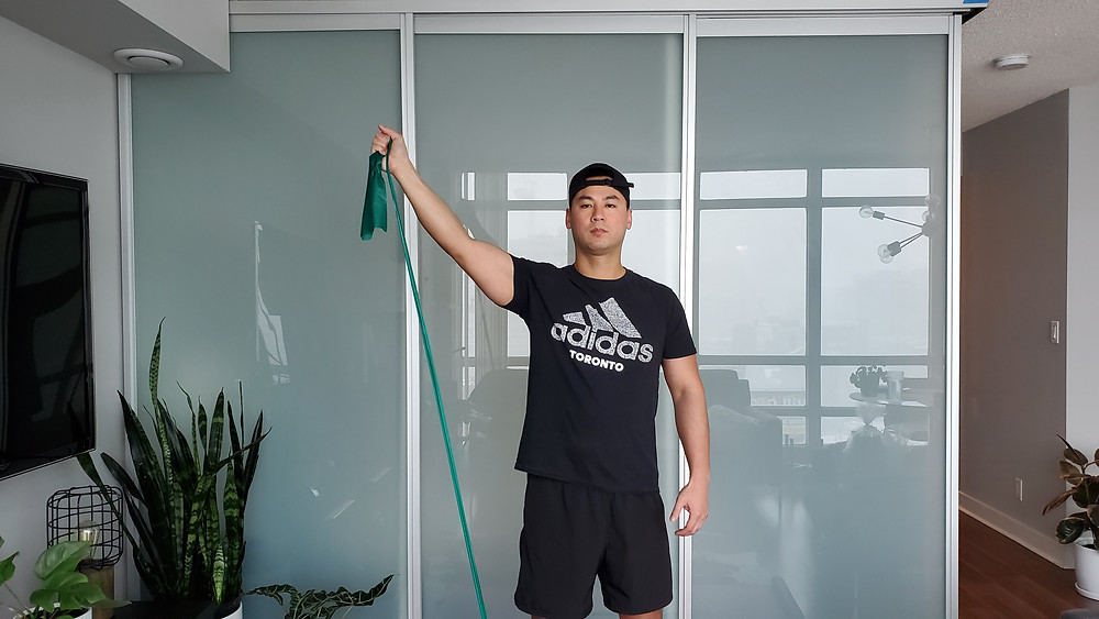 Physiotherapist demonstrating scaption raise exercise