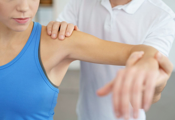Physiotherapist assessing a woman who has shoulder pain