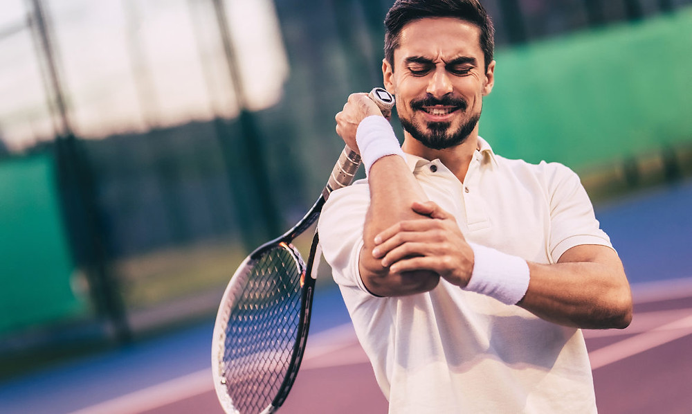 Tennis player grimacing in pain as he rubs his elbow