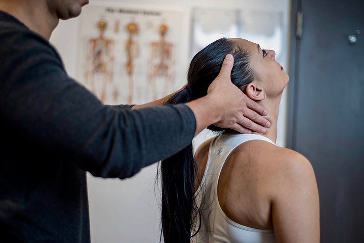 Physiotherapist assessing patient's neck