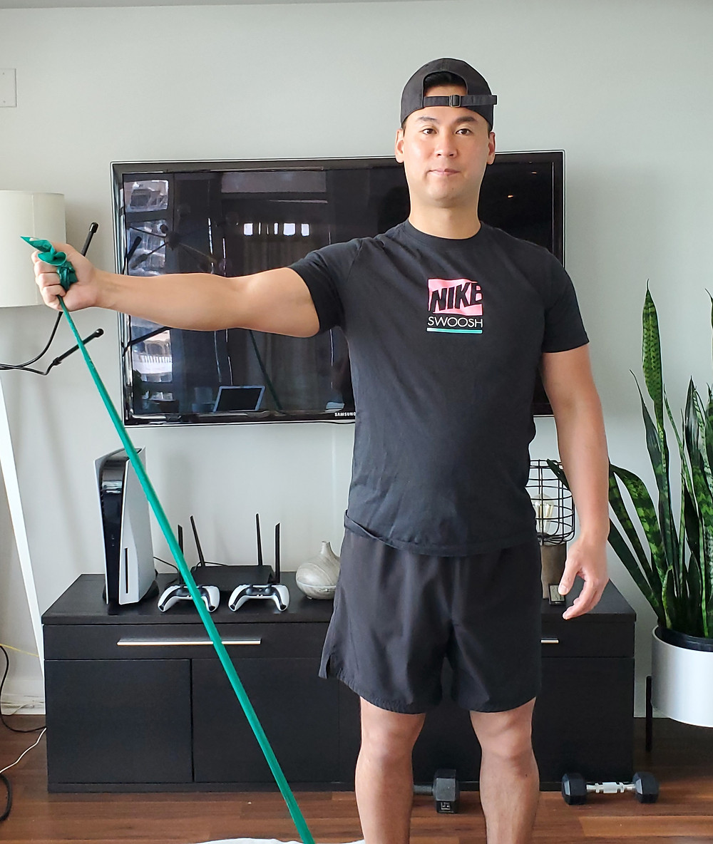 Man performing a shoulder exercise using a resistance band