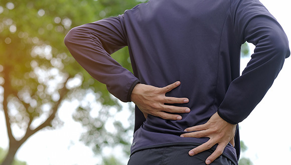 Man rubbing his sore lower back standing at a park
