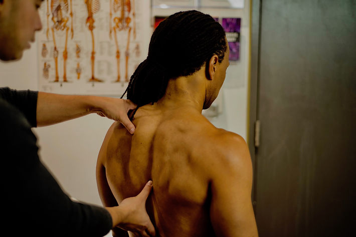 Physiotherapist assessing patient's upper back