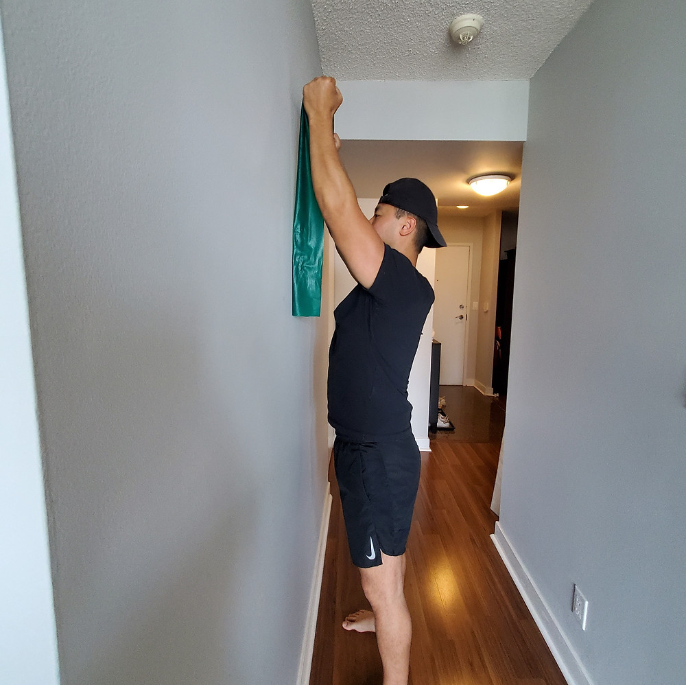 Physiotherapist performing shoulder isometric rotation wall slide exercise