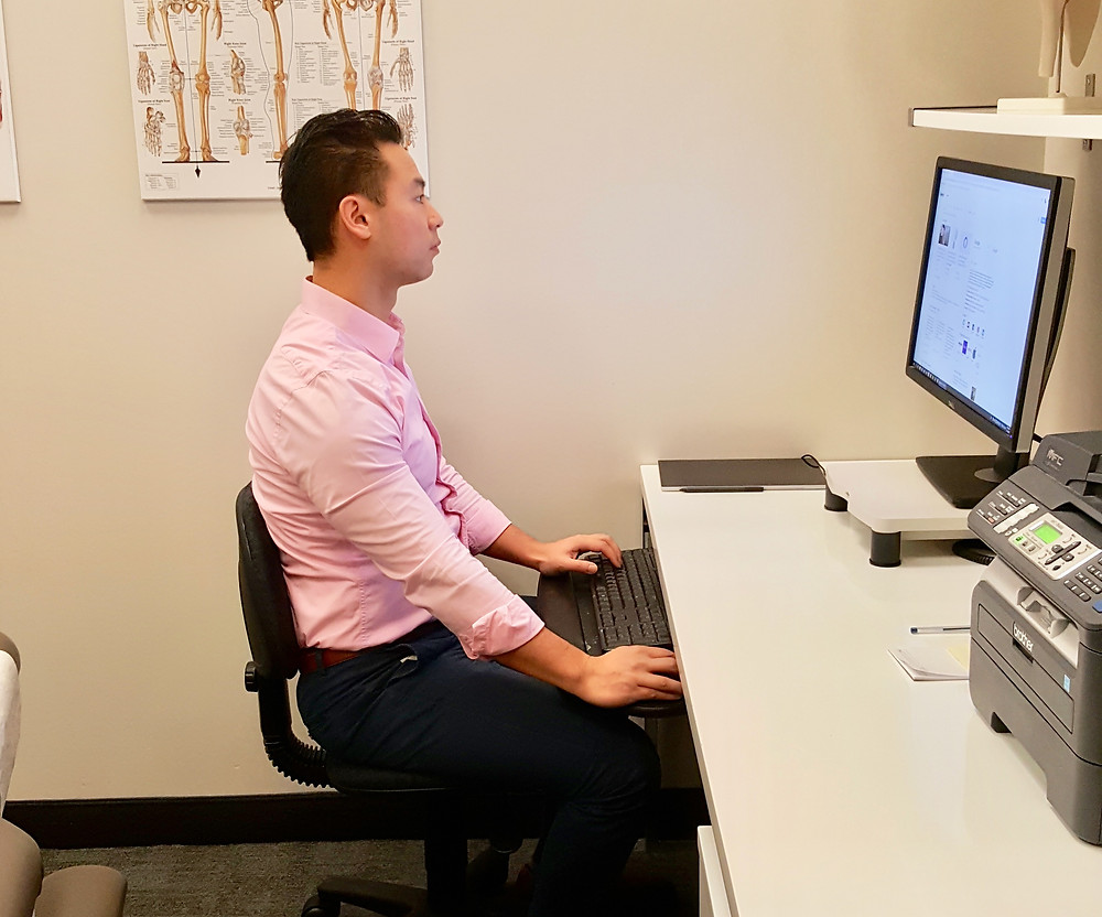 Rebuild physiotherapy Eric Lau demonstrating proper posture at work desk