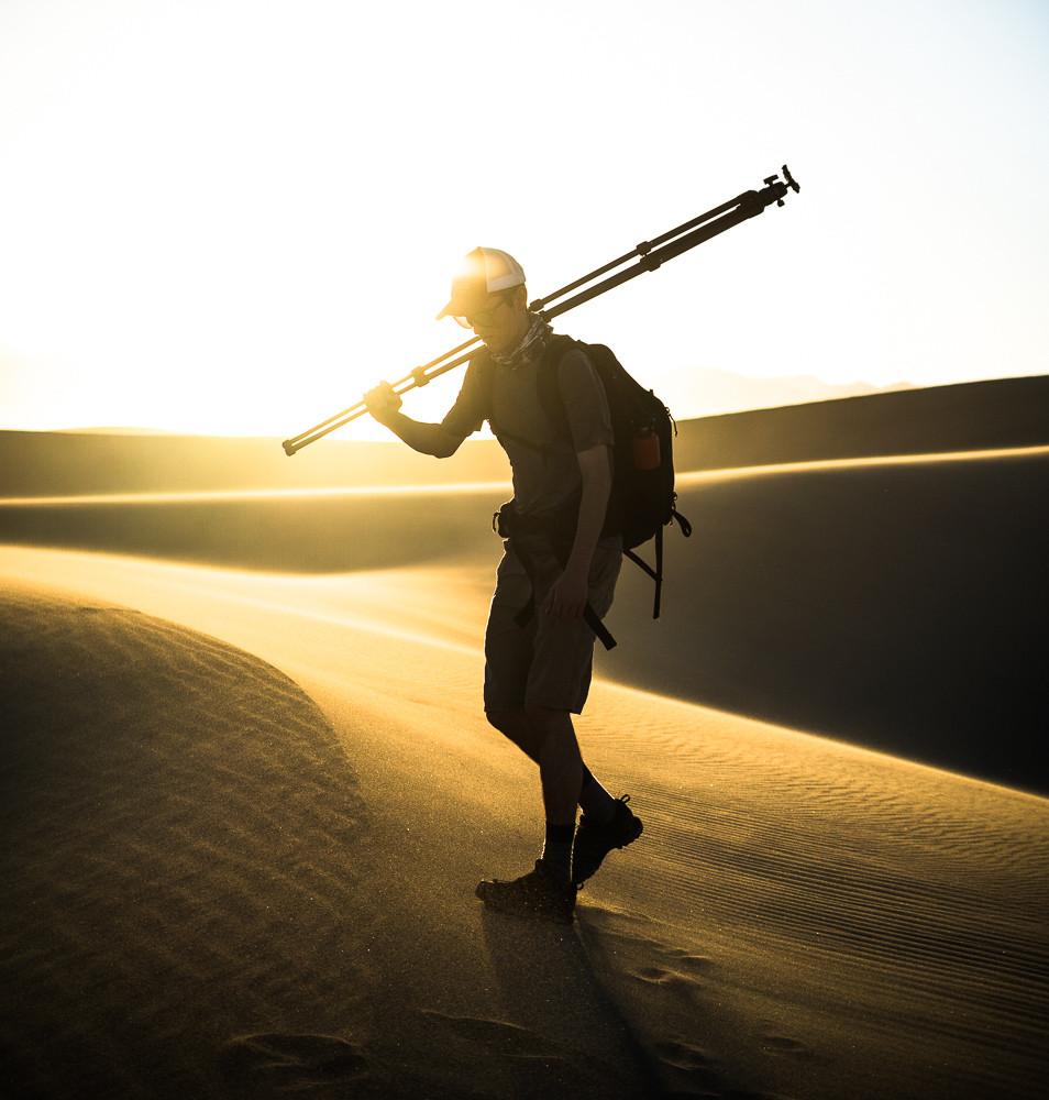 Hiker in Death Valley carrying Slik CF-833 tripod.
