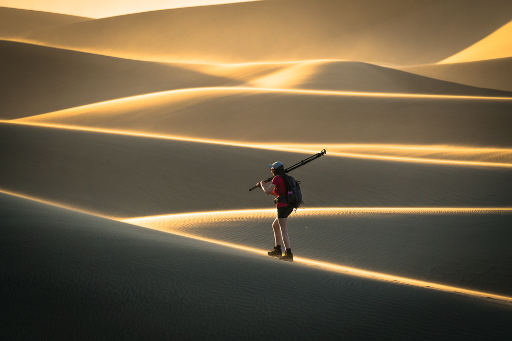 Hiker in Death Valley National Park carrying a tripod.