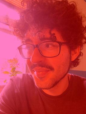 Foto do autor. Usa óculos, cabelo encaracolado