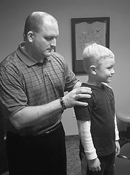 Dr. Schemmel evaluating a young boy for chiropractic treatment. Safe and effective.