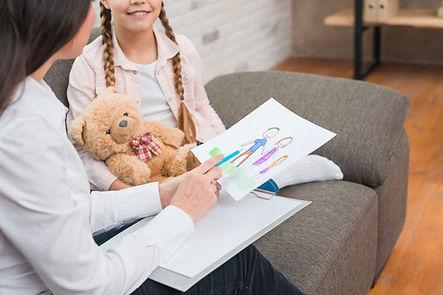 terapia psicológica infantil, niña y psicóloga con peluche y dibujo