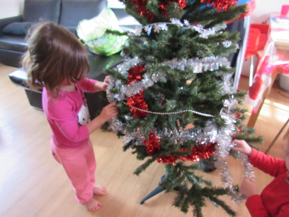 enfant qui décore sapin