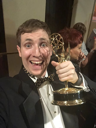 Ben Ratner Holding An Emmy Award While Wearing A Tuxedo