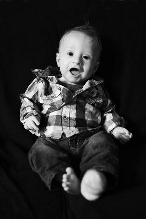 bebe habille en chemise et pantalon dans studio noir et blanc photographe bébé nouveau-né naissance