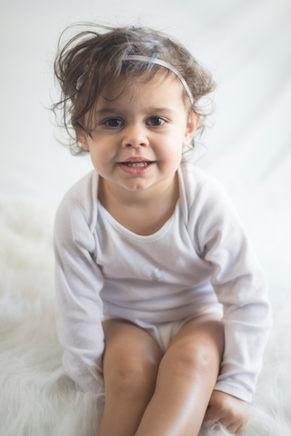 petite fille souriant fond blanc studio photographe bébé nouveau-né naissance