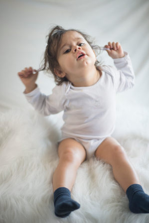 shooting enfant fond studio blanc et tapis fourrure photographe bébé nouveau-né naissance