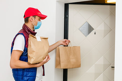 Delivery man holding paper bag with food