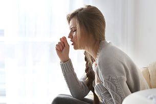 Young ill woman sitting on lounge at hom