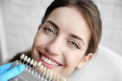 Young woman choosing color of teeth at dentist.jpg