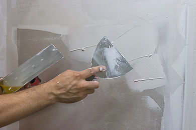 man hand with trowel plastering a wall,