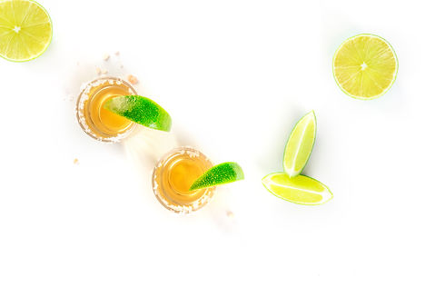 Golden tequila with lime slices on a whi