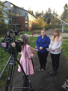 two women prepare to give video interview while producer talks to them