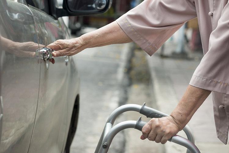 senior woman open car door with walker o