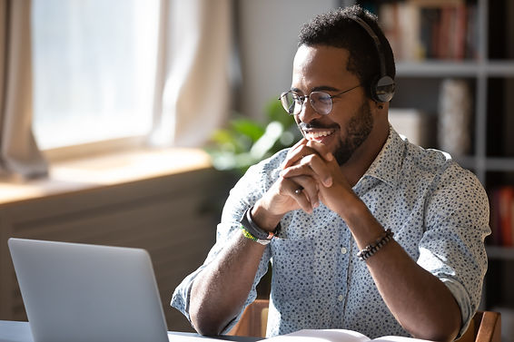Happy millennial african american man in glasses wearing headphones, enjoying watching edu