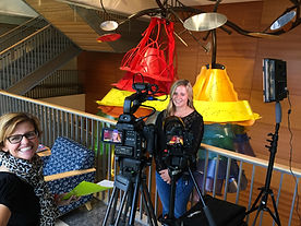 Two women smile while filming with large video camera.