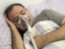 Man Lying On Bed With Sleeping Apnea And