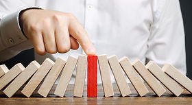 Businessman stops collapse domino effect
