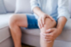Man suffering from knee pain sitting sof