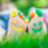 Couple lying on green grass. Children ha