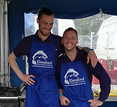 Two men wearing blue aprons printed for Davies Catering