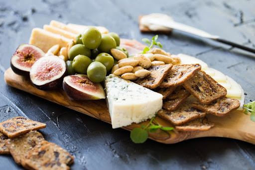 Designing your own charcuterie board with you and your partner's favorite sweets, cheeses, meats, berries, etc. will make your decor that much more personal and fun.