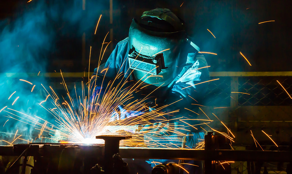 Person welding with sparks and blue lights