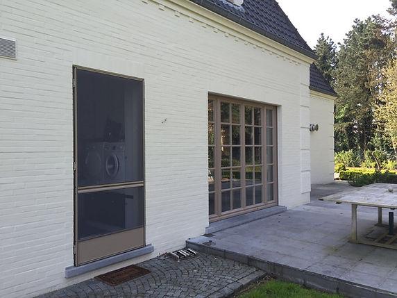 vliegendeur in taupe kleur bij witte gekaleid huis in rustieke stijl