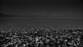 Kamienkový breh jazera večer. Slnečné jazerá v Senci.